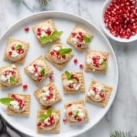 Hummus-Pomegranate TRISCUIT Toppers use just a handful of ingredients – hummus, feta and pomegranate seeds – to create a fun party snack for all ages!