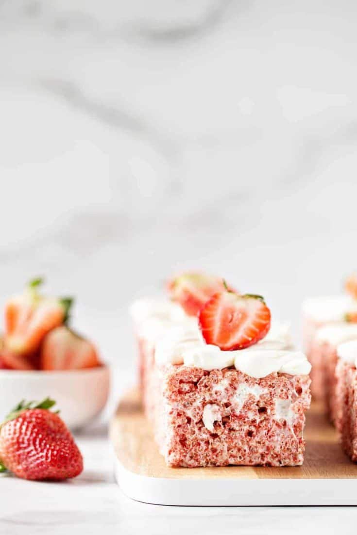 Strawberry Rice Krispie Treats are festively pink for Valentine's Day and full of fun strawberry flavor. Top them with pillowy buttercream frosting and sprinkles for an extra-special touch.