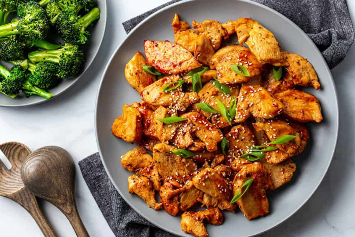 Serving platter of honey soy chicken next to a platter of cooked broccoli
