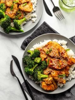 Two plates of honey soy chicken served with rice and broccoli