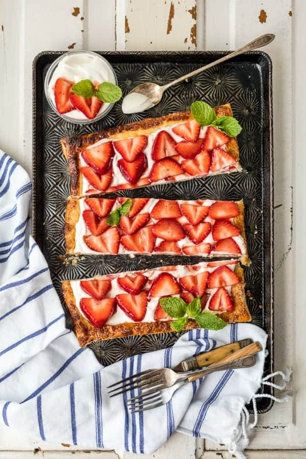 Overhead view of puff pastry strawberry tart on a baking sheet