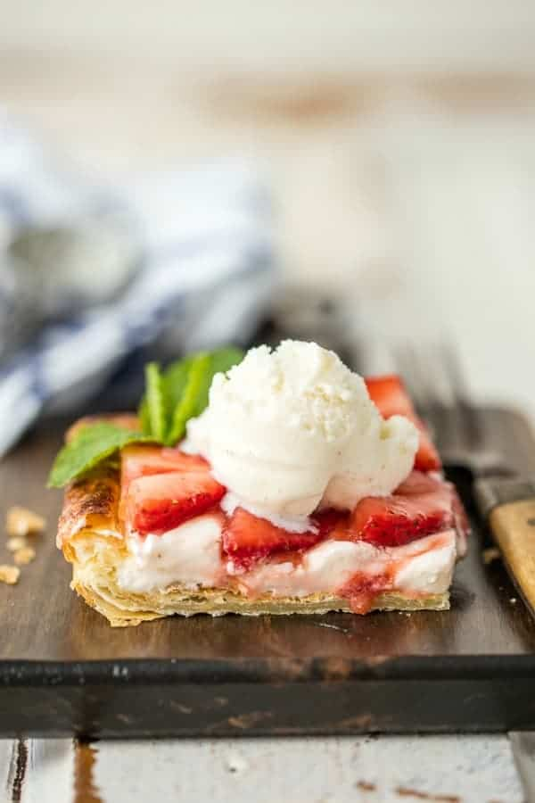 Puff pastry strawberry tart topped with vanilla ice cream and garnished with mint