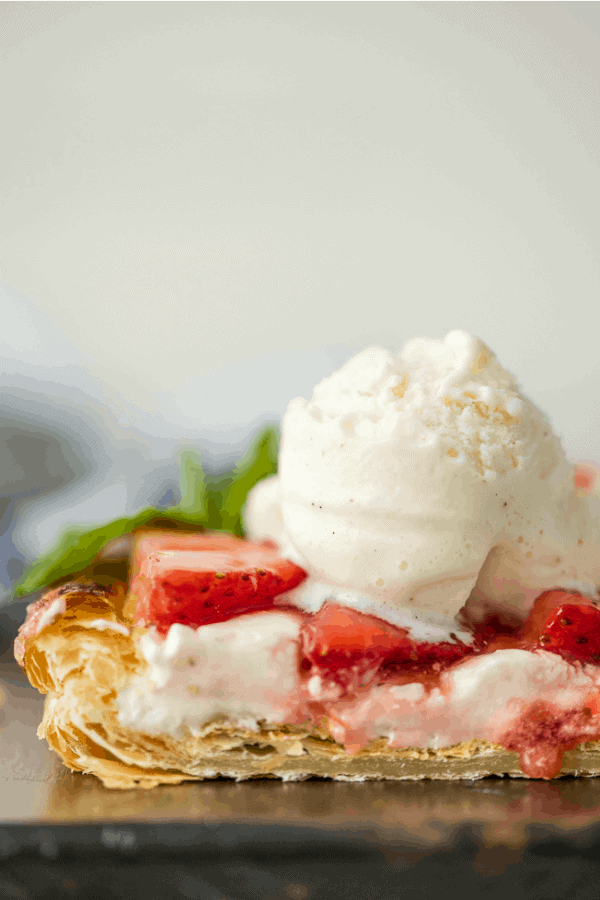 Close up of sliced puff pastry strawberry tart topped with a scoop of vanilla ice cream