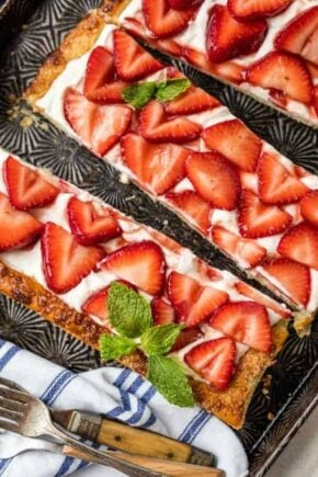 Slices of puff pastry strawberry tart garnished with mint