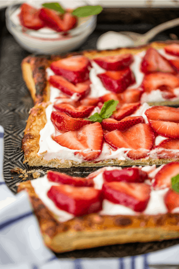 Sliced strawberries topping a puff pastry tart shell and mascarpone filling