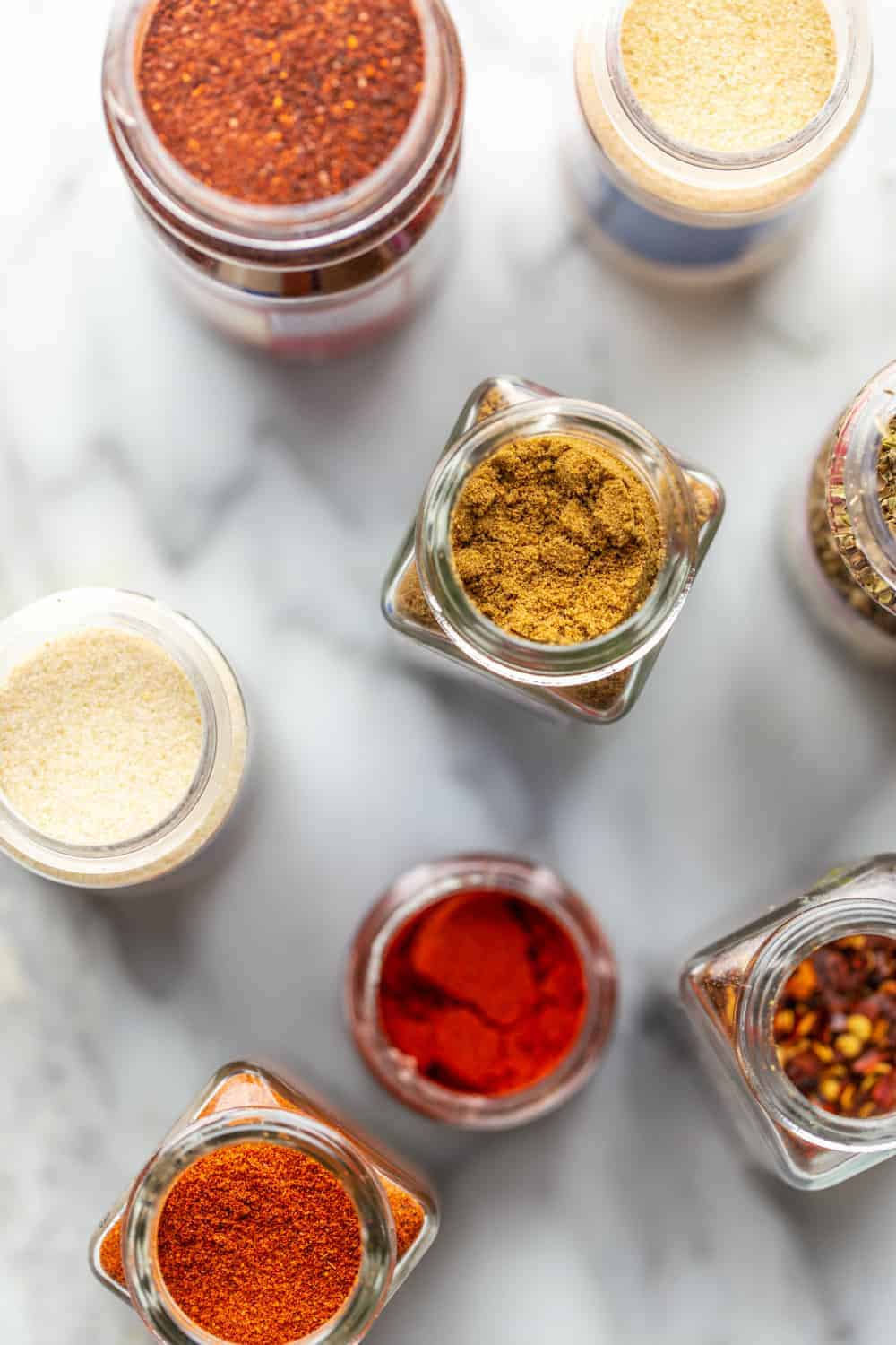 Overhead view of open spice jars for taco seasoning on a marble surface