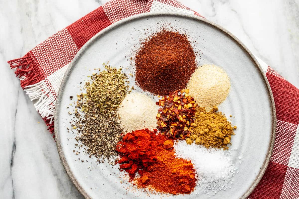Spices for homemade taco seasoning on a plate with a red dish towel