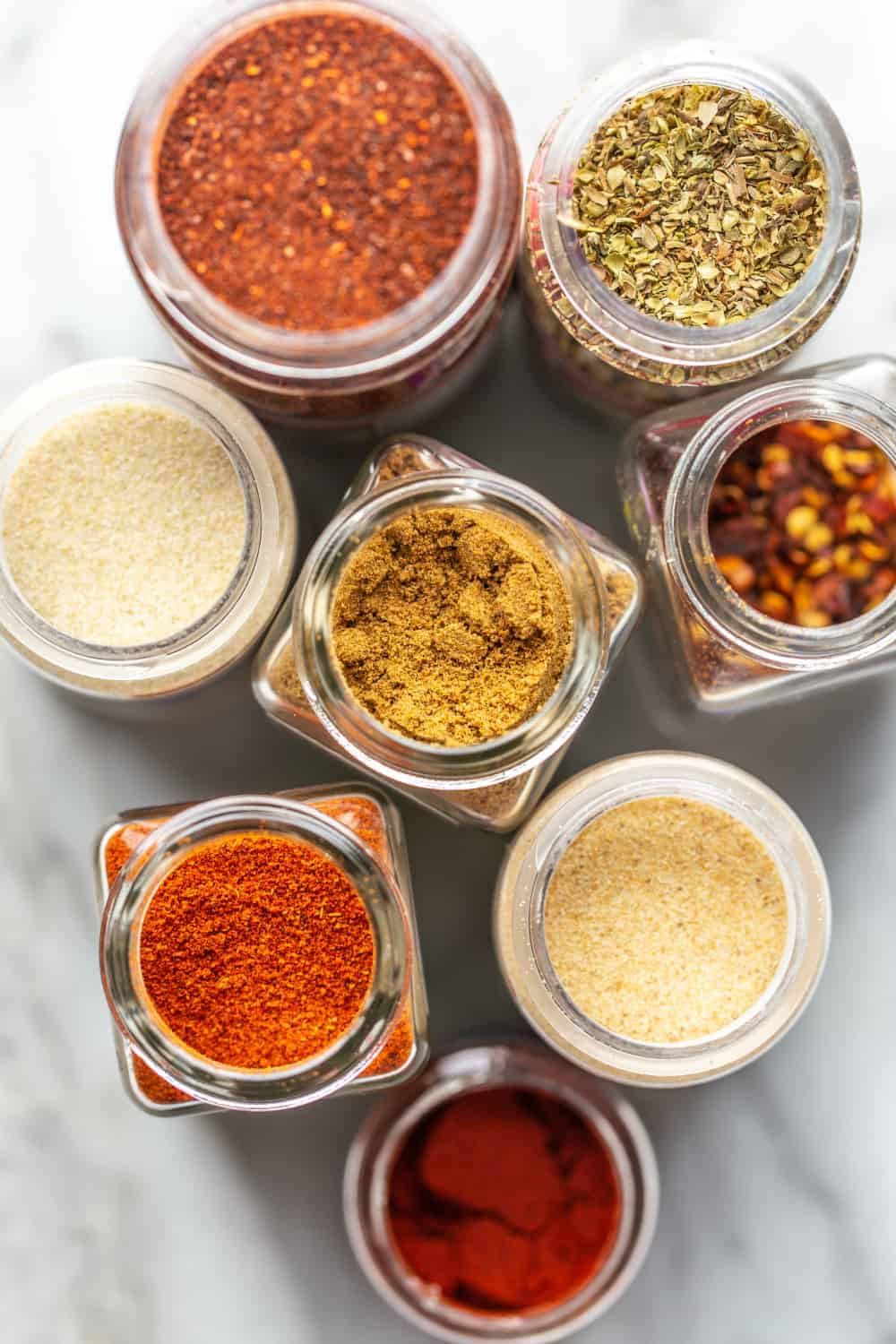 Overhead view of open spice jars for chili seasoning on marble surface