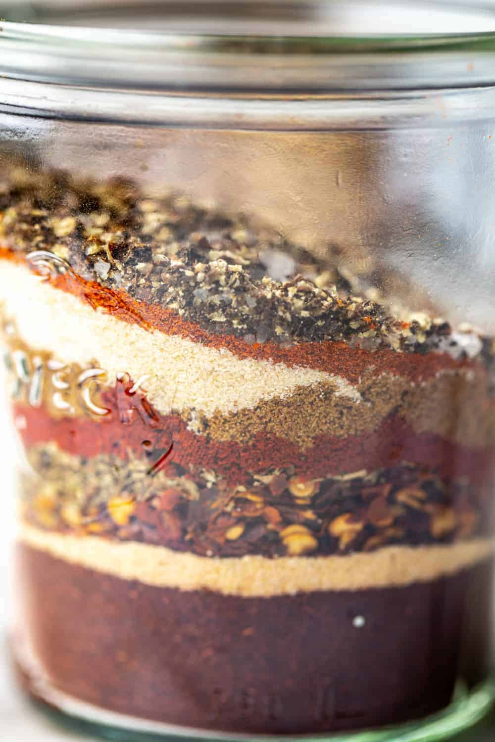 close-up view of spices for homemade taco seasoning layered in a jar