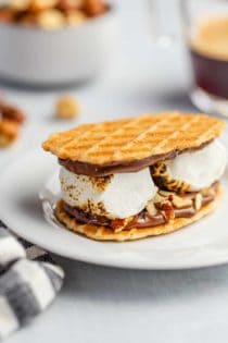 Plated s'more made with waffle cookies, chocolate hazelnut spread and 2 large roasted marshmallows