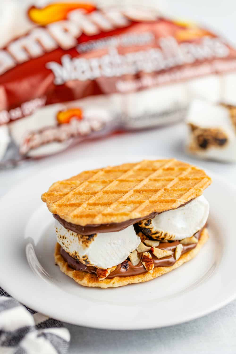 Toasted Hazelnut S'more made with waffle cookies with bag of marshmallows in the background