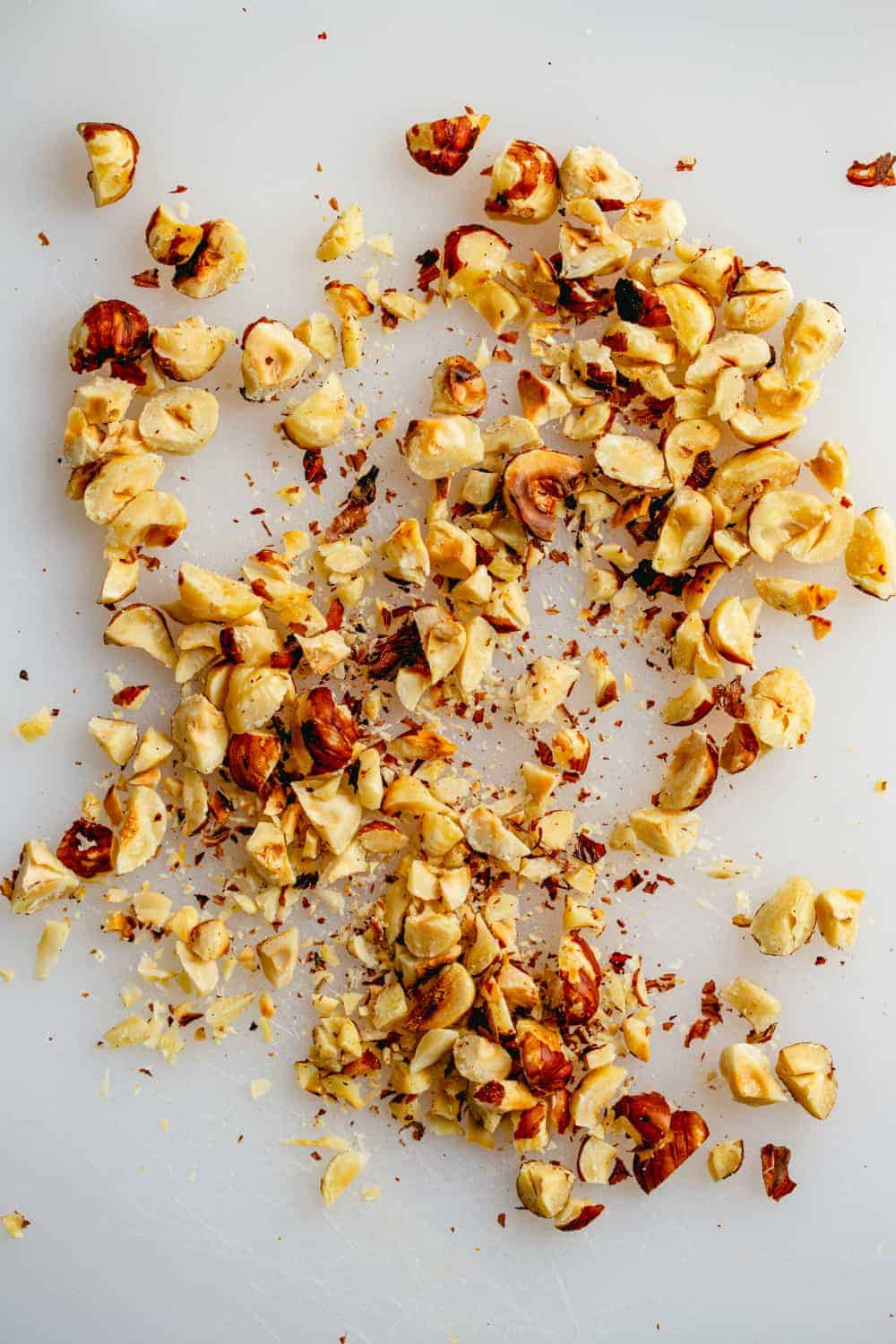 Chopped toasted hazelnuts on a white surface