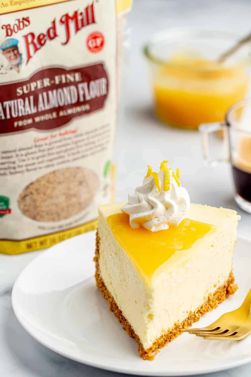Plated lemon cheesecake next to bag of finely ground almond meal with bowl of lemon curd in the background