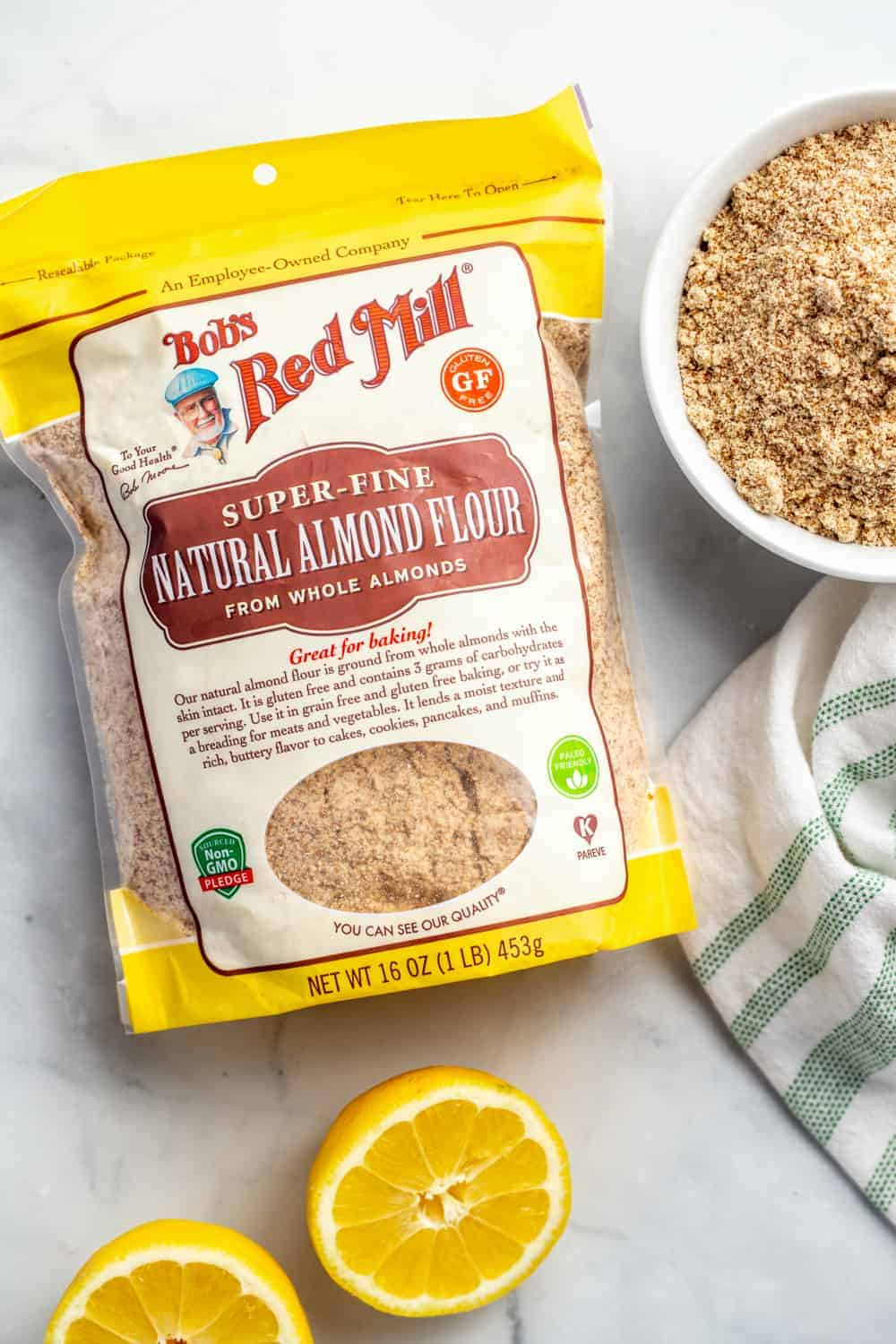 Bag of finely ground almond meal next to a bowl of almond meal and halved lemons