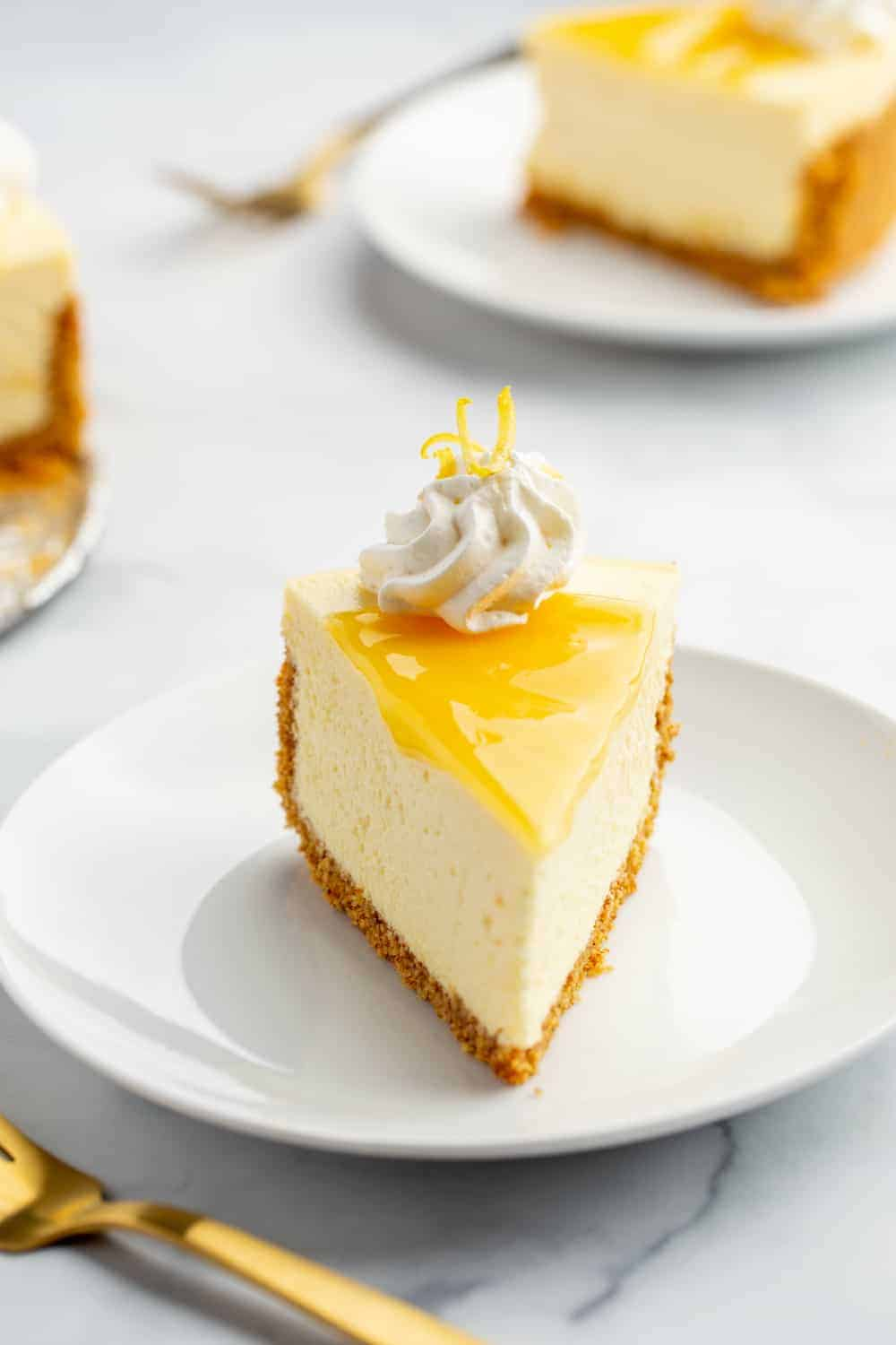 Front view of a slice of lemon cheesecake topped with lemon curd and whipped cream