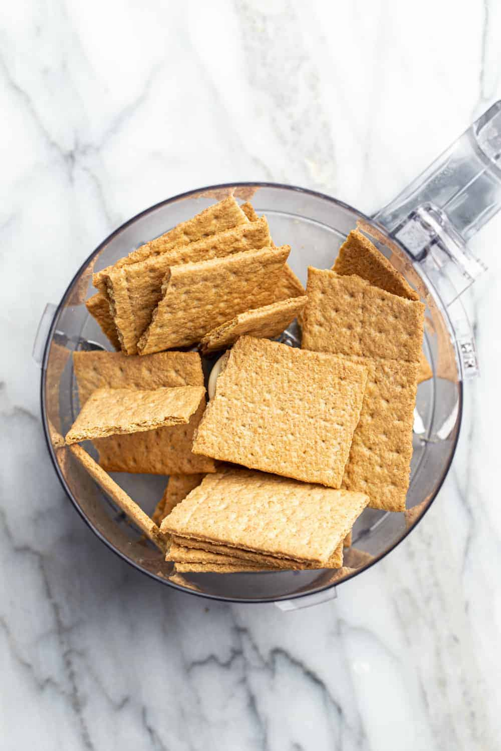 Graham crackers in the bowl of a food processor on a marble surface