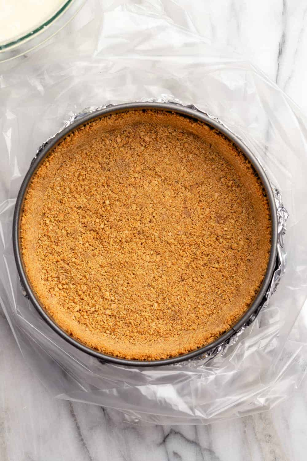 Baked graham cracker crust in a springform pan, ready to add cheesecake filling
