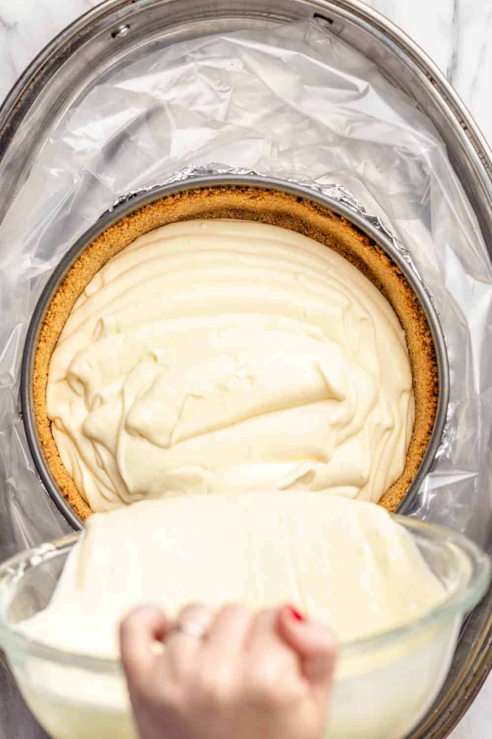 Pouring cheesecake filling into a graham cracker crust before adding a water bath