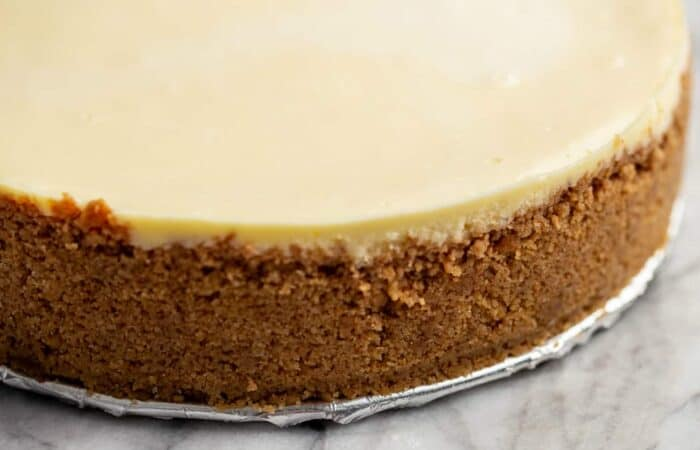 Close-up of baked graham cracker crust on a baked cheesecake