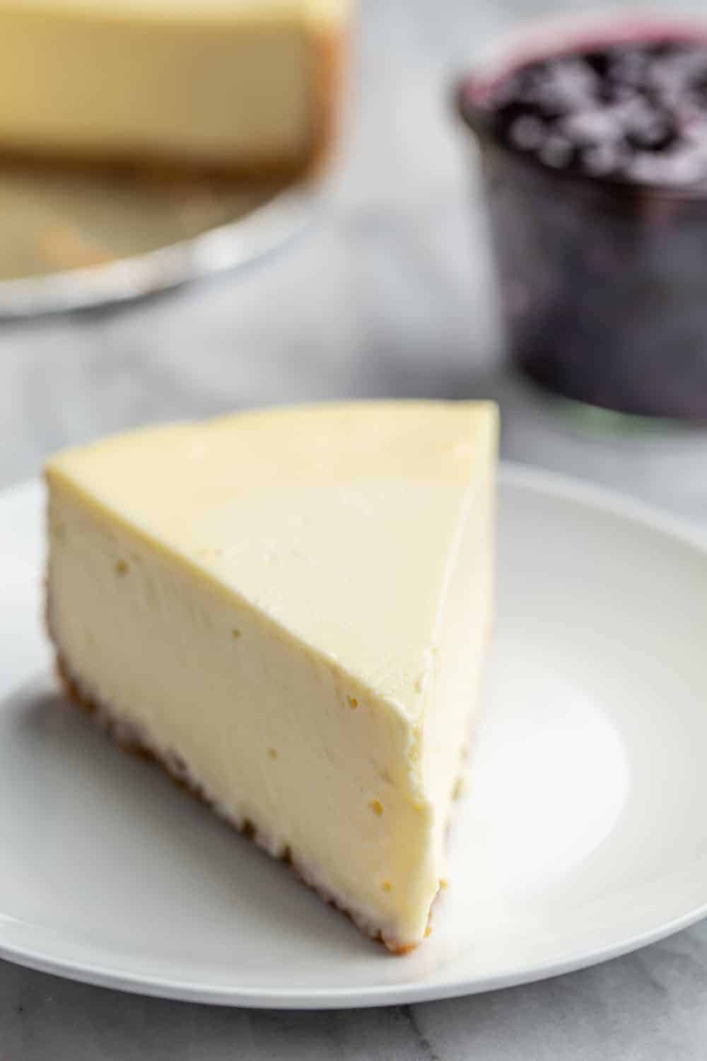 Slice of plain vanilla cheesecake on a white plate