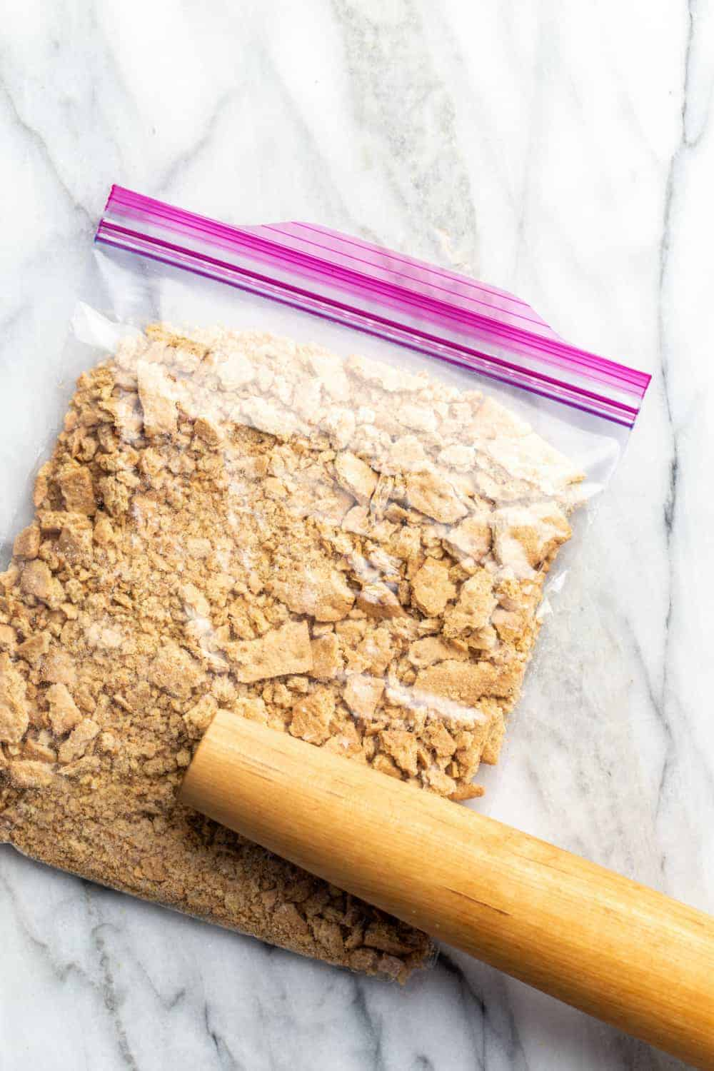 Rolling pin crushing graham crackers in a zip-top bag into crumbs