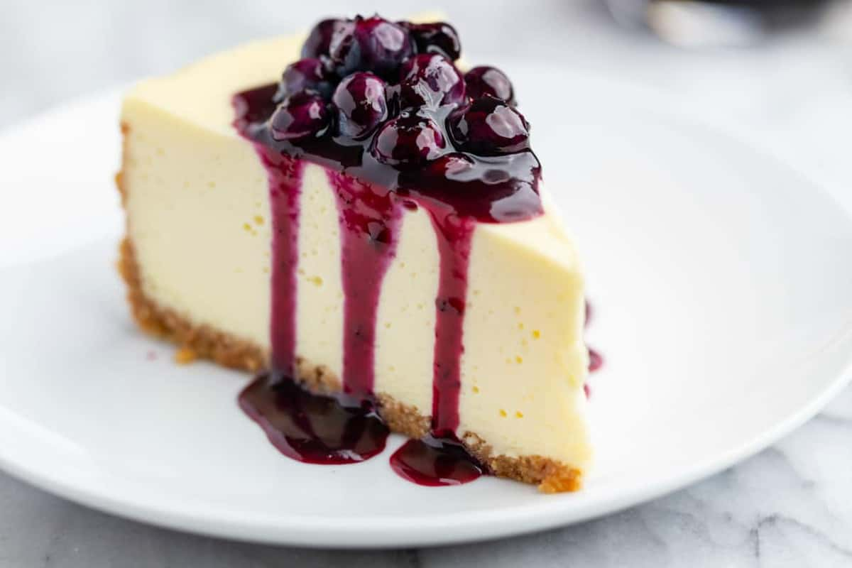 Slice of vanilla cheesecake topped with blueberry sauce