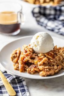 Caramel apple crisp topped with a scoop of vanilla ice cream on a white plate
