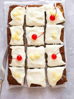 Pineapple cake topped with cream cheese frosting and cut into slices, topped with cherries and pineapple