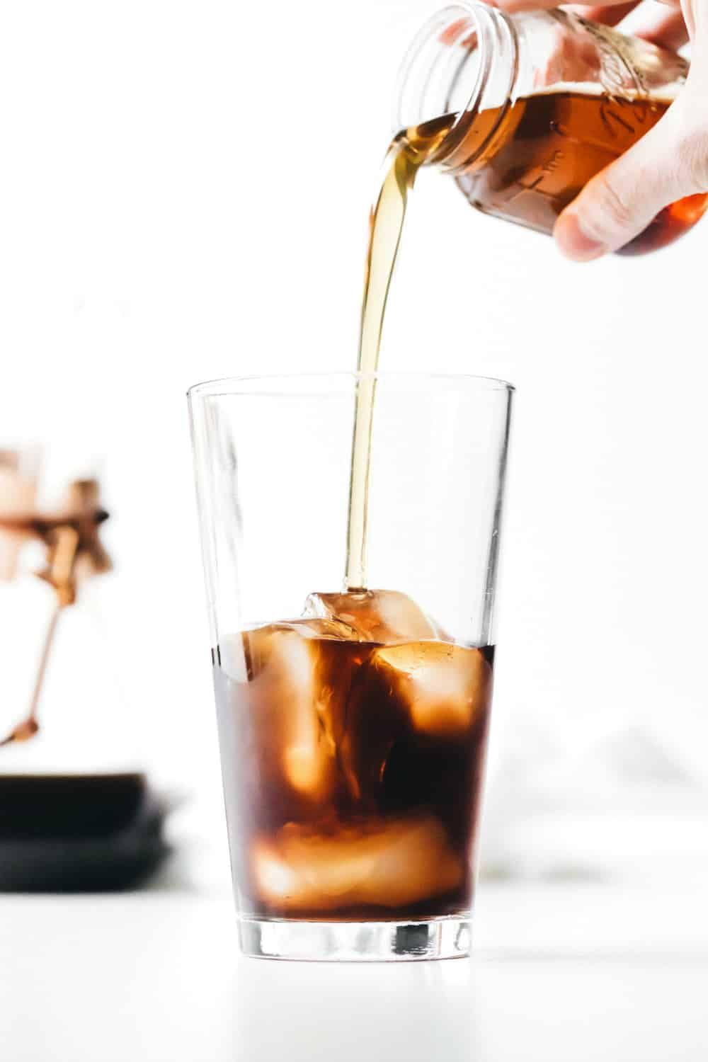 Adding vanilla coffee syrup to a glass of iced coffee