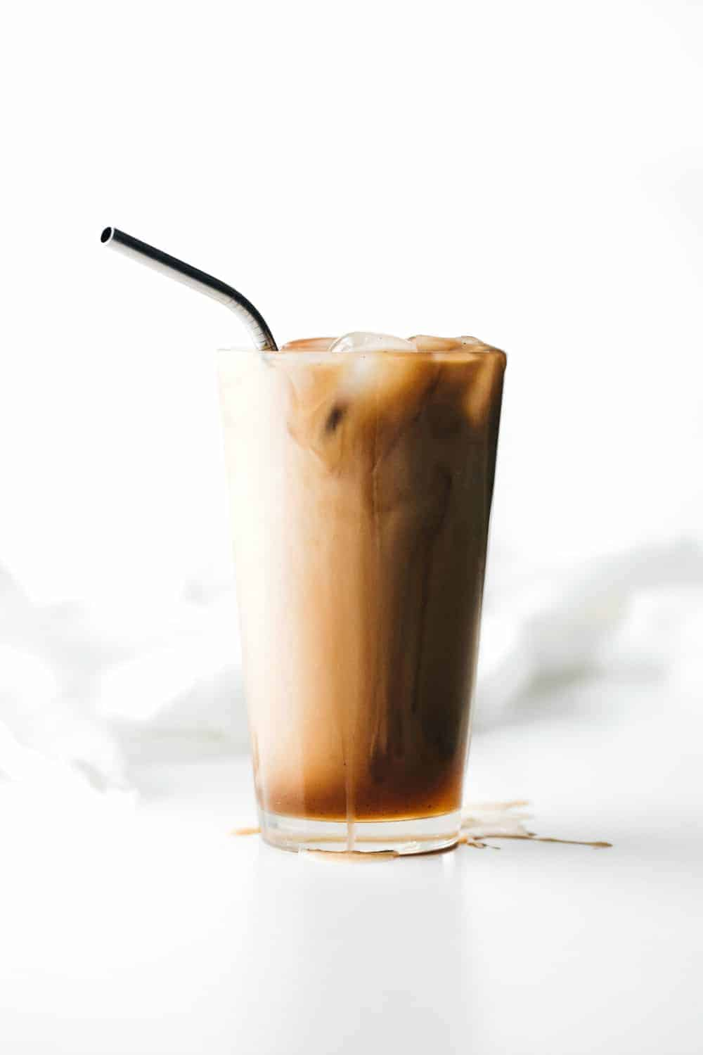 Glass of vanilla iced coffee with a straw