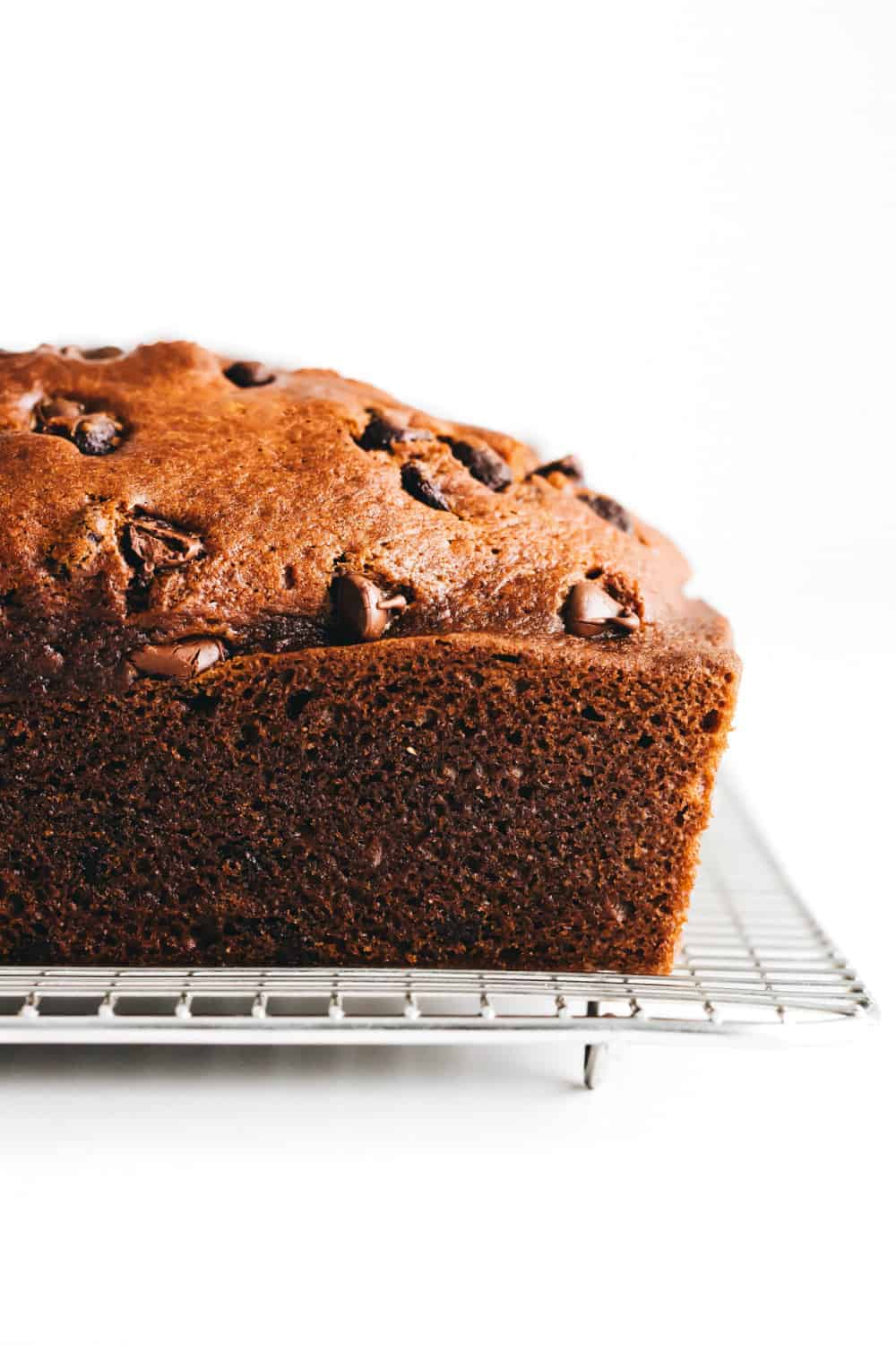 Side view of a loaf of pumpkin chocolate chip bread on a cooling rack
