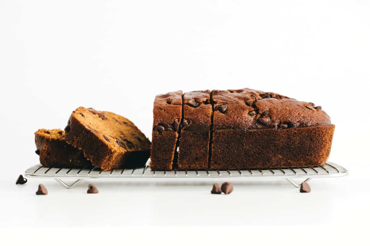Side view of a sliced loaf of pumpkin chocolate chip bread on a cooling rack
