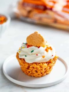 Plated marshmallow treat cupcake topped with a pumpkin spice marshmallow and sprinkles