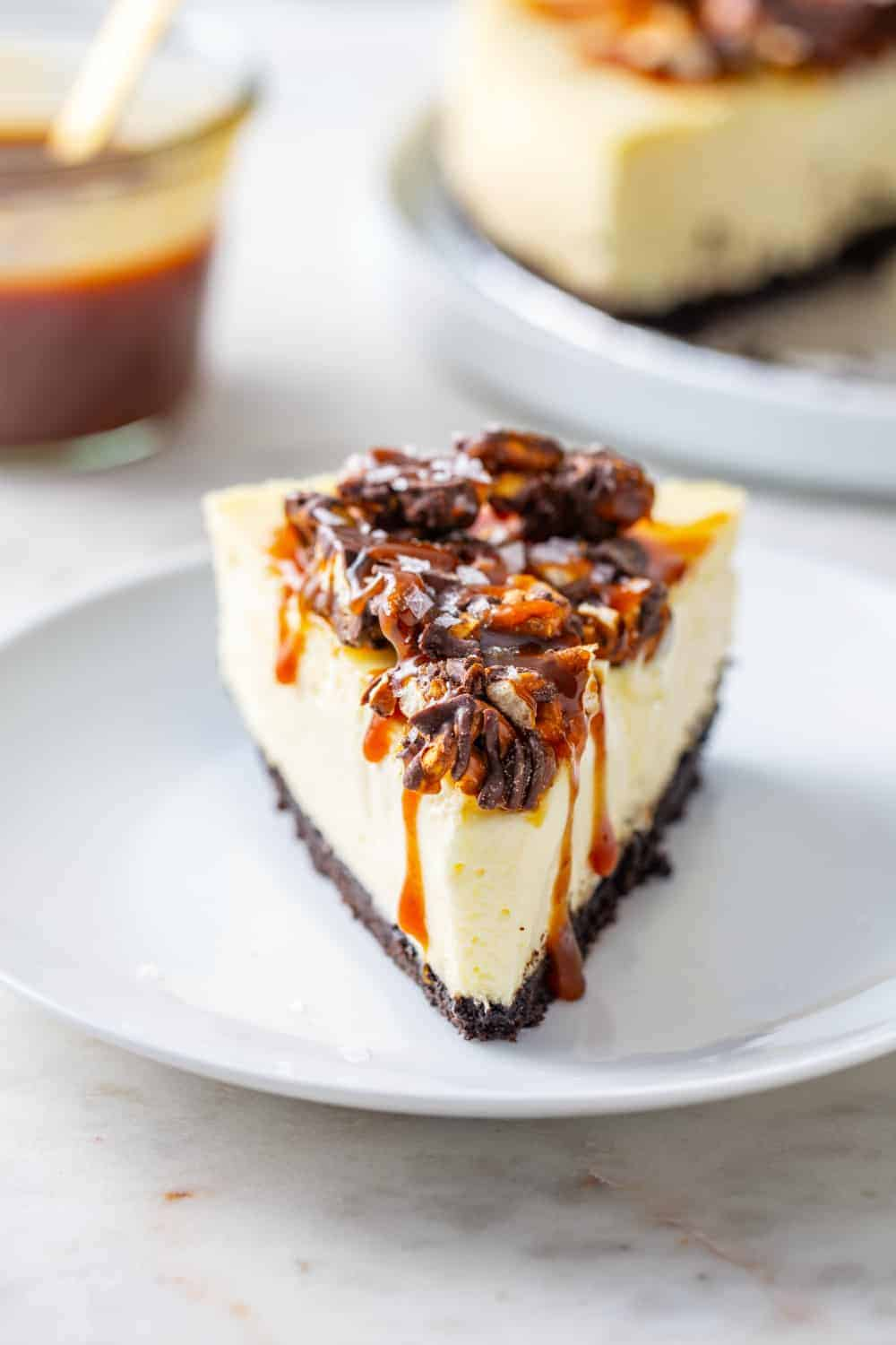 Slice of sweet and salty cheesecake on a white plate with a jar of caramel in the background