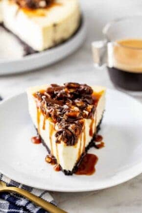Slice of sweet and salty cheesecake with the remaining cheesecake in the background