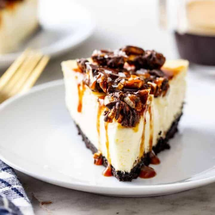 Slice of cheesecake topped with caramel sauce and chopped pretzels