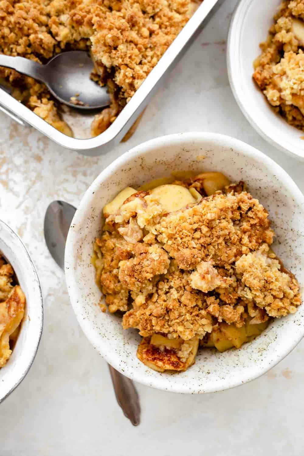 Pan of old fashioned apple crisp surrounded by small bowls of crisp