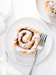 Plated maple chai cinnamon roll on a white plate