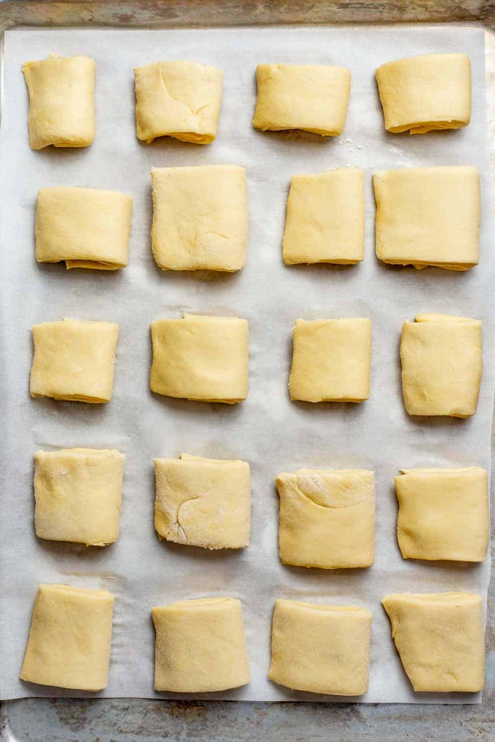 Shaped parker house rolls on a parchment-lined baking sheet
