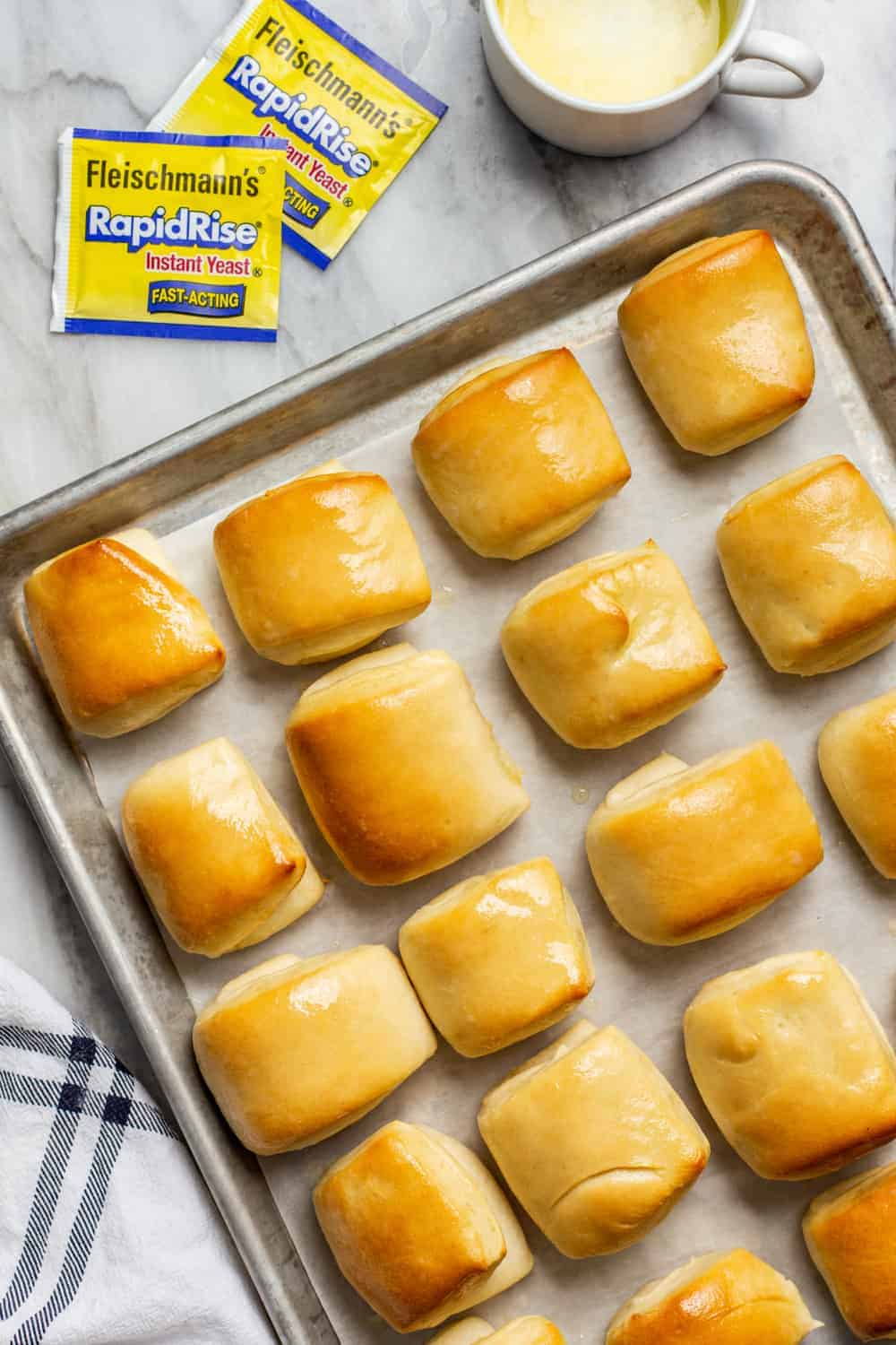 Baked parker house rolls on a baking sheet, freshly brushed with butter