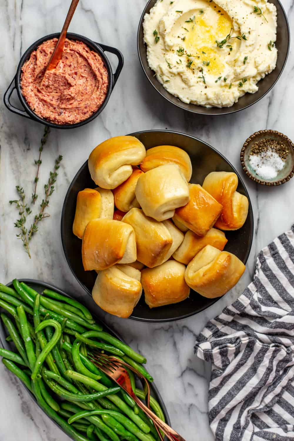 Thanksgiving dinner sides on a marble surface: a bowl of green beans, a bowl of mashed potatoes, and a small bowl of cranberry butter surrounding parker house rolls