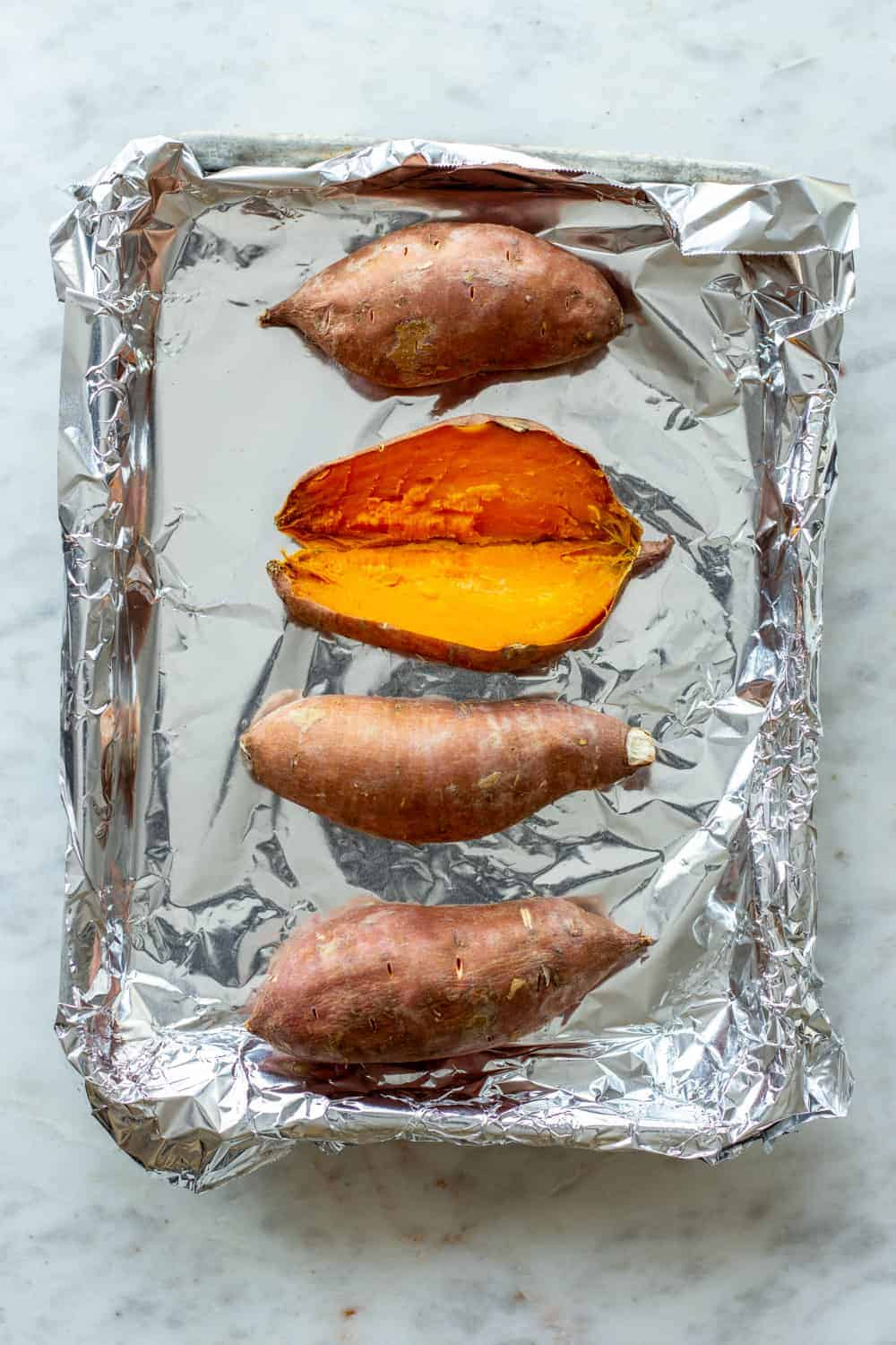 Baked sweet potatoes on a foil-lined sheet tray, with one of the sweet potatoes split open