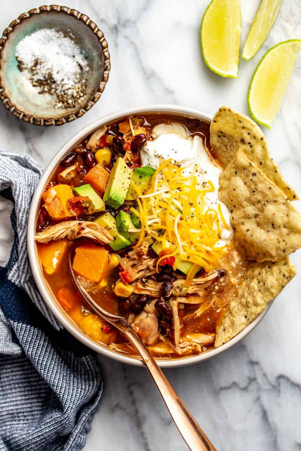 Bowl of tortilla soup made with rotisserie chicken. Garnished with tortilla chips, cheese and sour cream