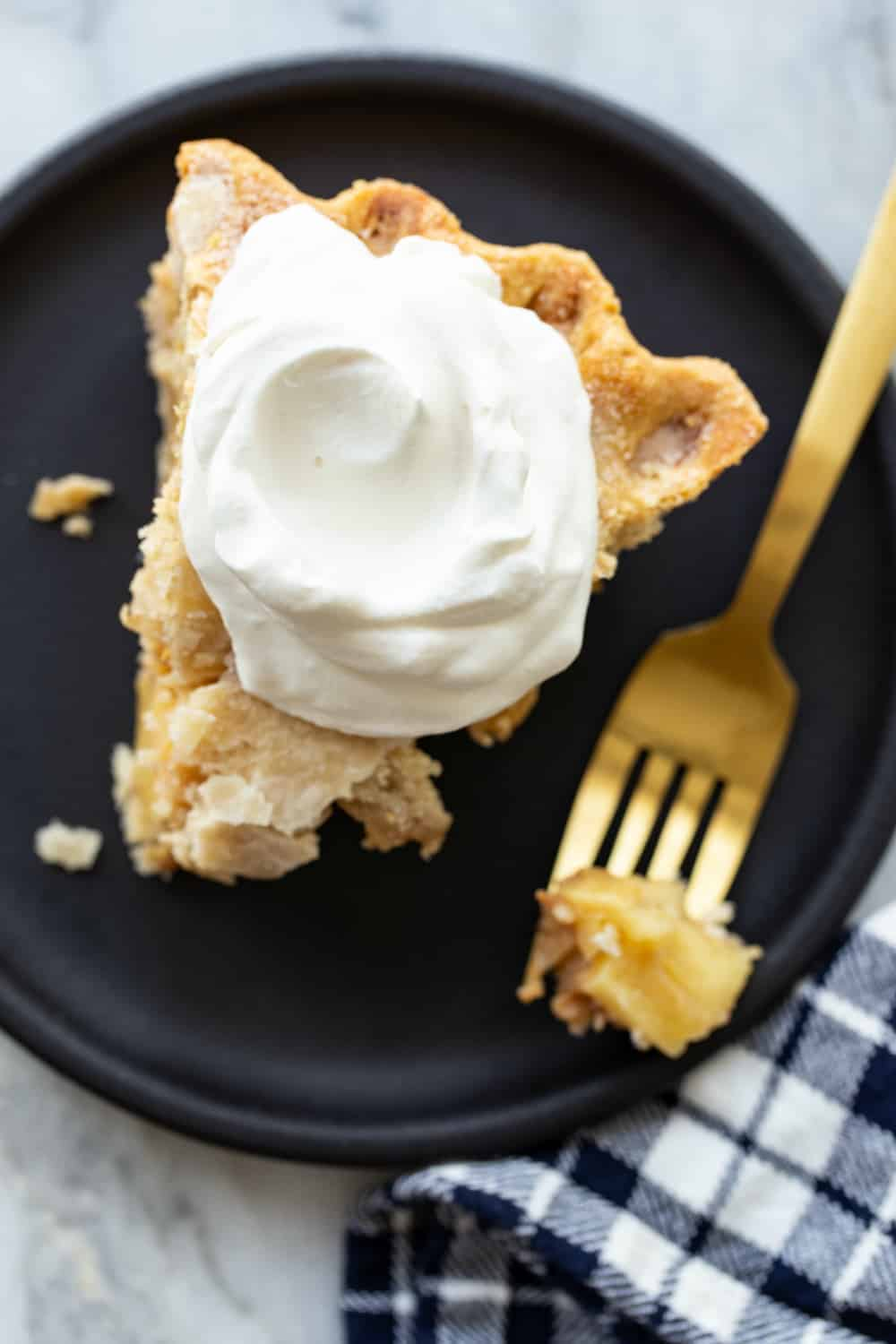 Slice of apple pie on a black plate, topped with softly whipped cream