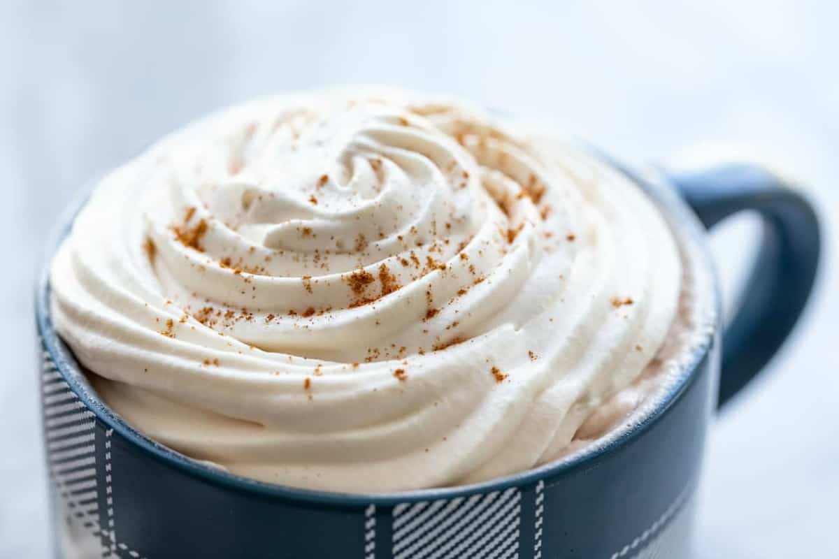 Close-up view of homemade whipped cream on a cup of coffee