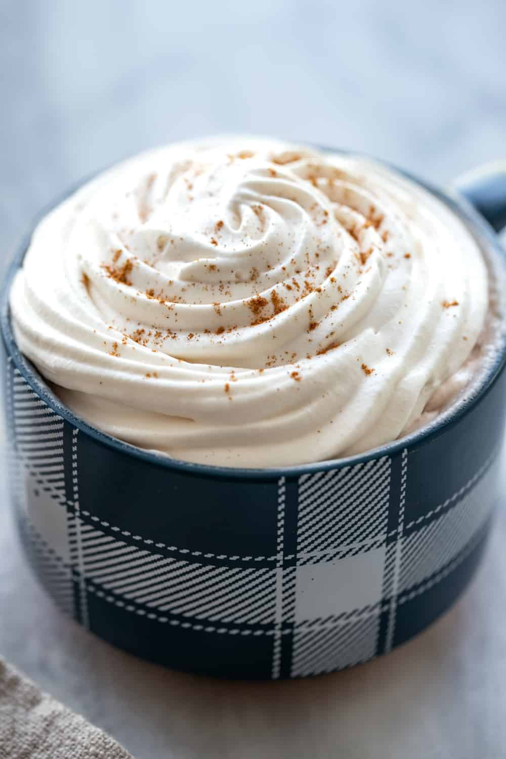 Coffee topped with homemade whipped cream in a blue mug