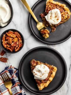 Slices of pecan pie on black plates arranged next to a bowl of pecans and a bowl of whipped cream