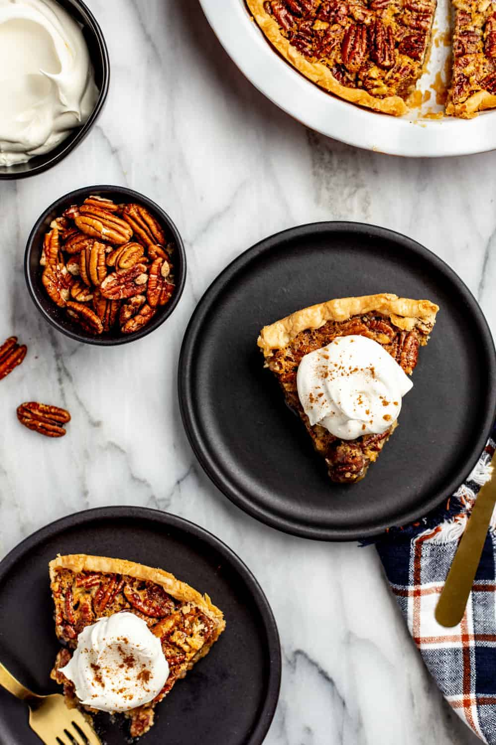 Overhead view of several plated pieces of classic pecan pie, topped with whipped cream