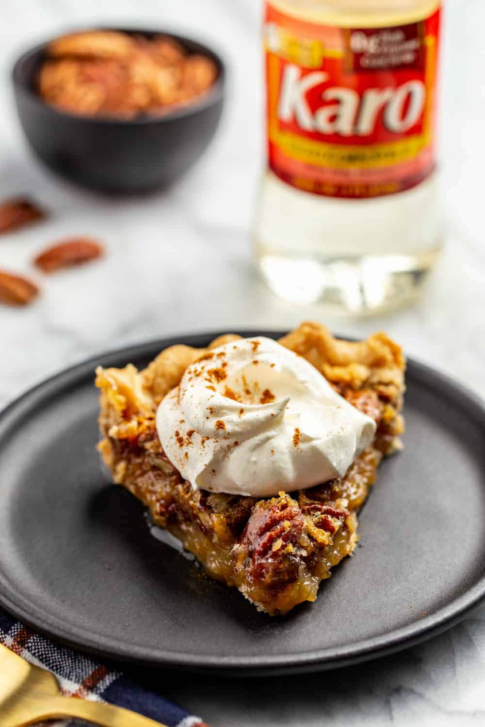 Slice of classic pecan pie on a black plate, topped with whipped cream