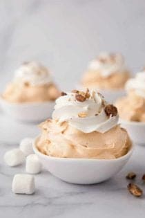 White bowls of pumpkin spice fluff garnished with whipped topping